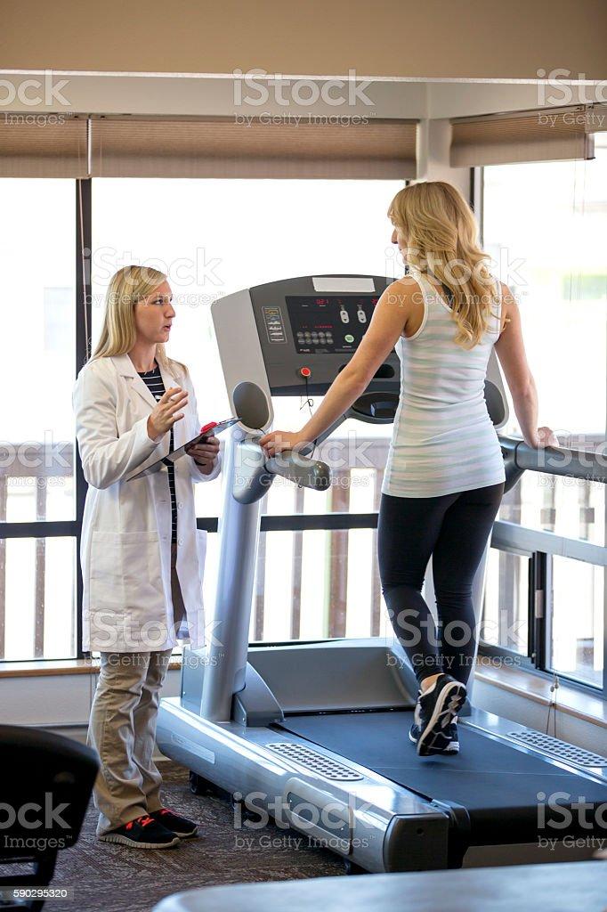 Young physical therapist explaing to a patient royaltyfri bildbanksbilder