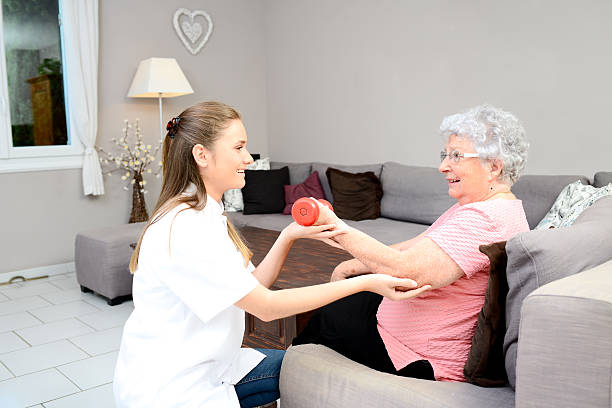 young physiotherapist nurse helping elderly women physical rehabilitation at home - geriatría fotografías e imágenes de stock