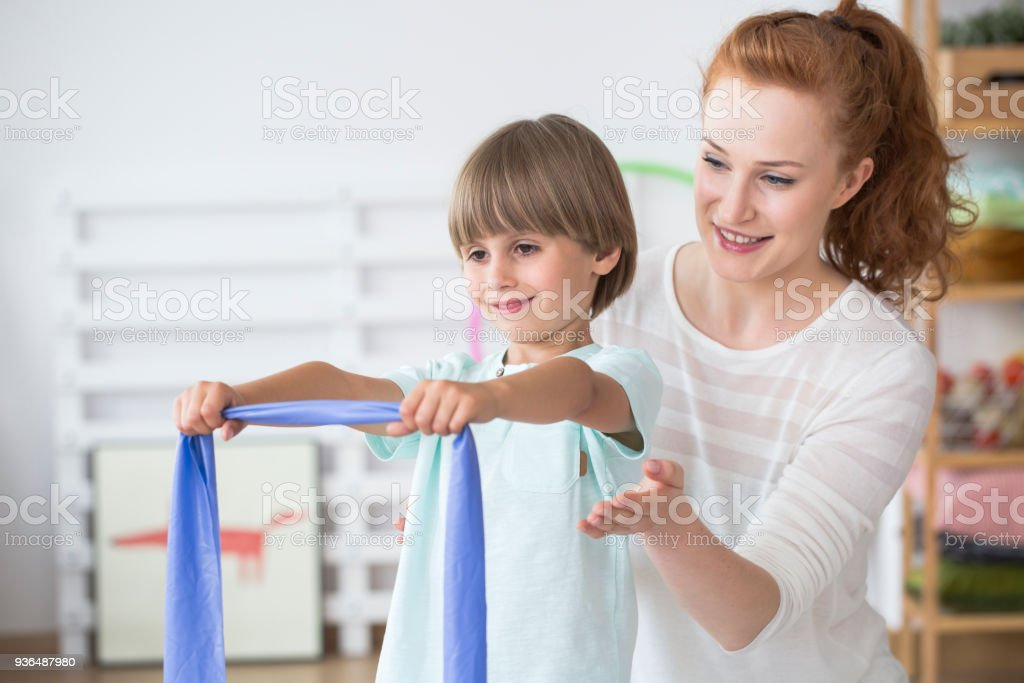Young physiotherapist with boy stock photo