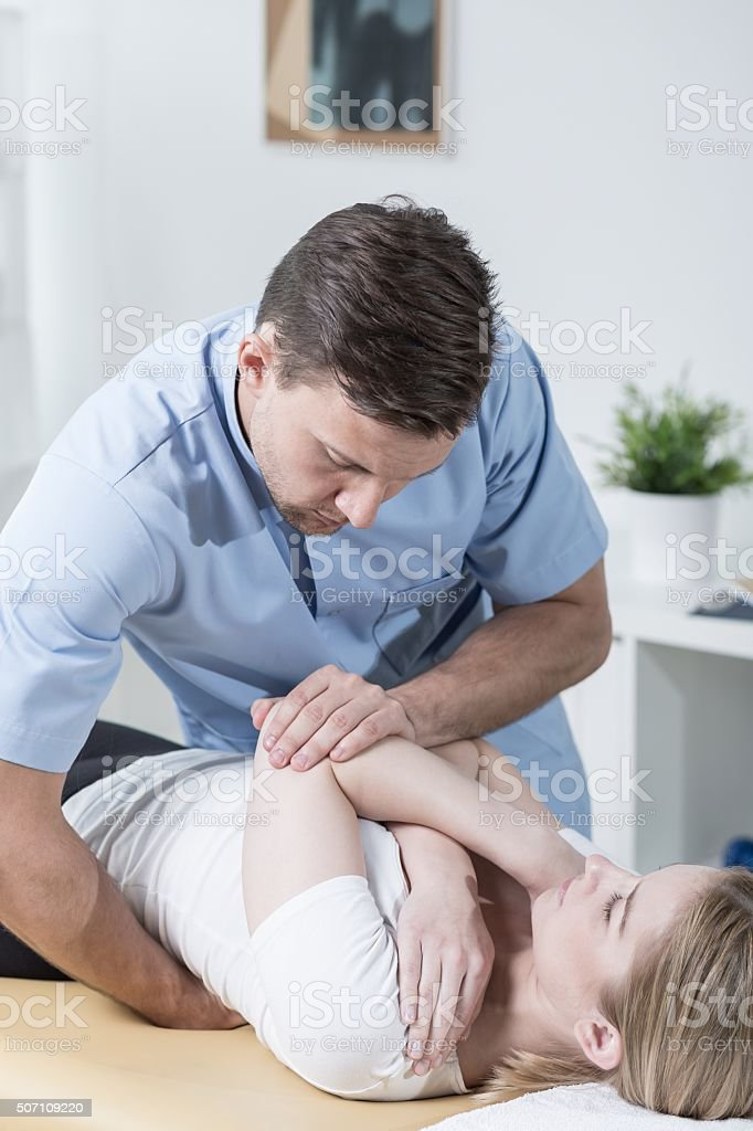 Young physiotherapist with patient stock photo
