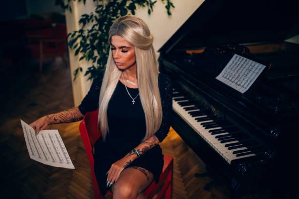 junger pianist spielt klavier und noten lesen - musiknoten tattoos stock-fotos und bilder
