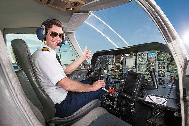 young pilot in aircraft cockpit giving thumbs up - pilot stock photos and pictures