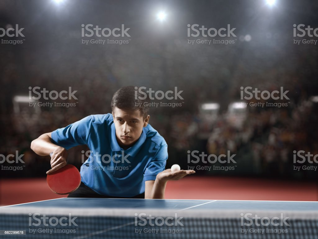 Young ping pong player playing table tennis game. He is holding a red...