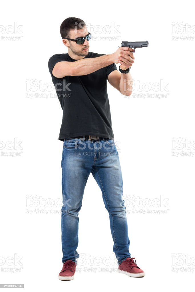 Young plain clothes policeman with sunglasses aiming gun away. stock photo