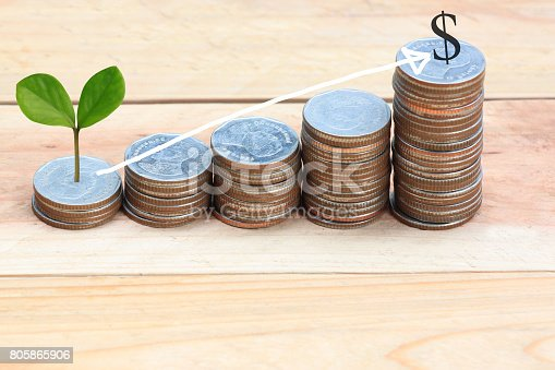 istock Young plant grown to stack silver coin in business growth concept on wood floor and Arrow points to top. 805865906