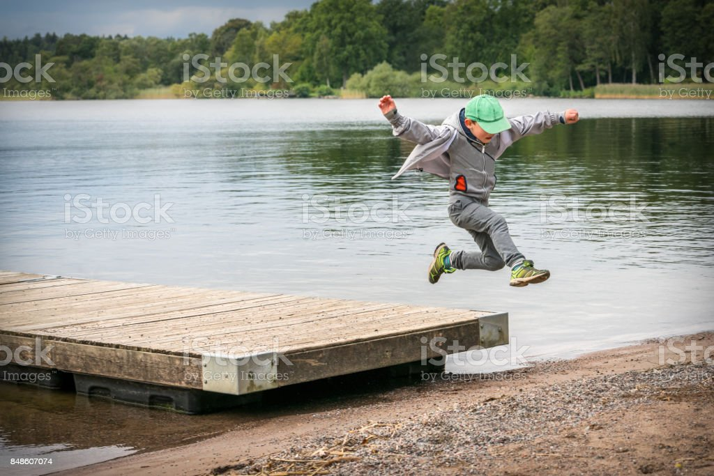 Young playful caucasian boy running in mid-air making a jump from a jetty to the beach. stock photo
