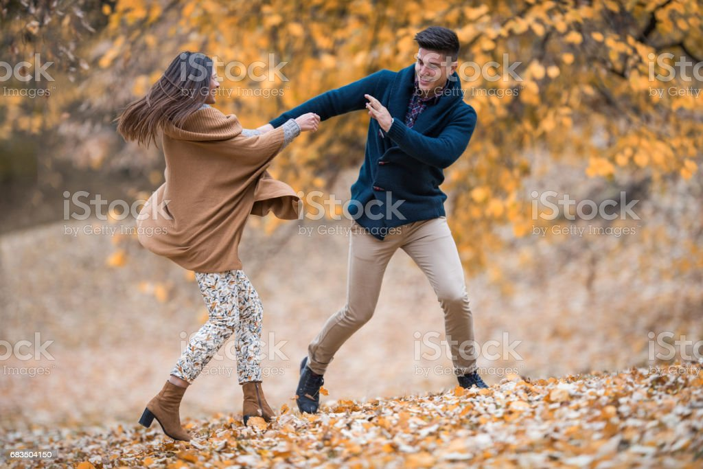 Young playful couple having fun in autumn day at the park. stock photo