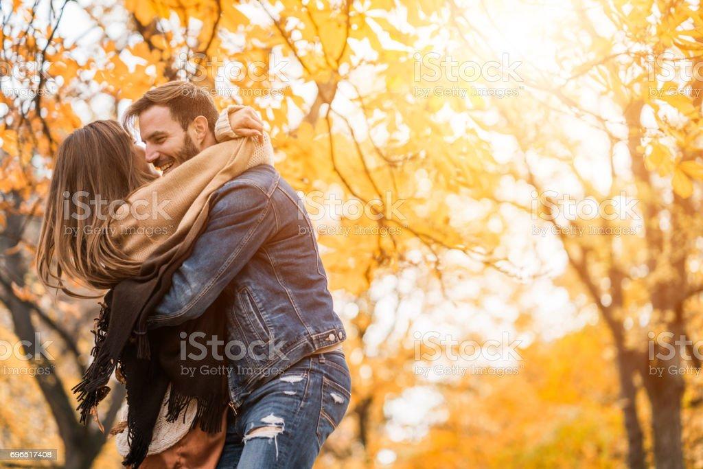 Jovem casal lúdico se divertindo no dia de outono. - foto de acervo