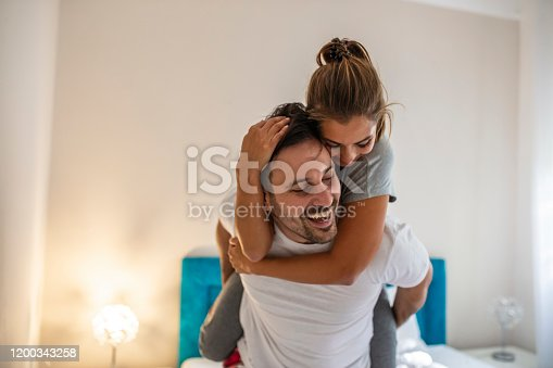 Always happy together. Young couple having fun in bedroom at home while handsome man giving his girlfriend piggy back ride. Cheerful smiling couple in love hugging in the bedroom