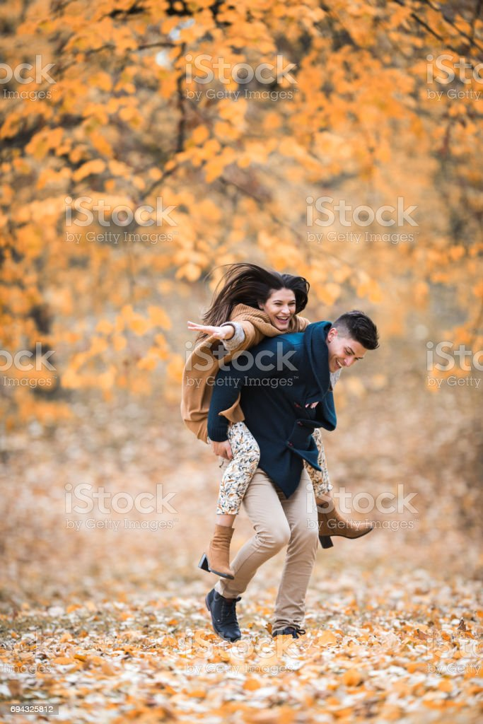 Young playful couple piggybacking and having fun in the park. stock photo