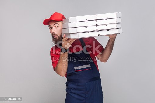 Young playful delivery man with beard in blue uniform and red t-shirt standing, holding and peeping out stack of cardboard pizza boxes on grey background. Indoor, studio shot, isolated, copy space.