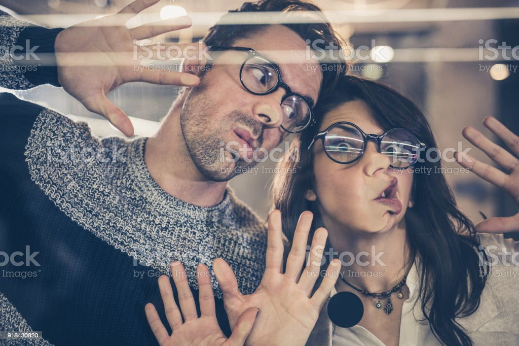 Young playful entrepreneurs making faces while playing on glass wall. foto stock royalty-free