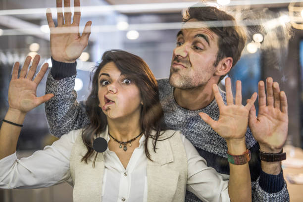 Young playful entrepreneurs making faces while playing with glass wall. stock photo