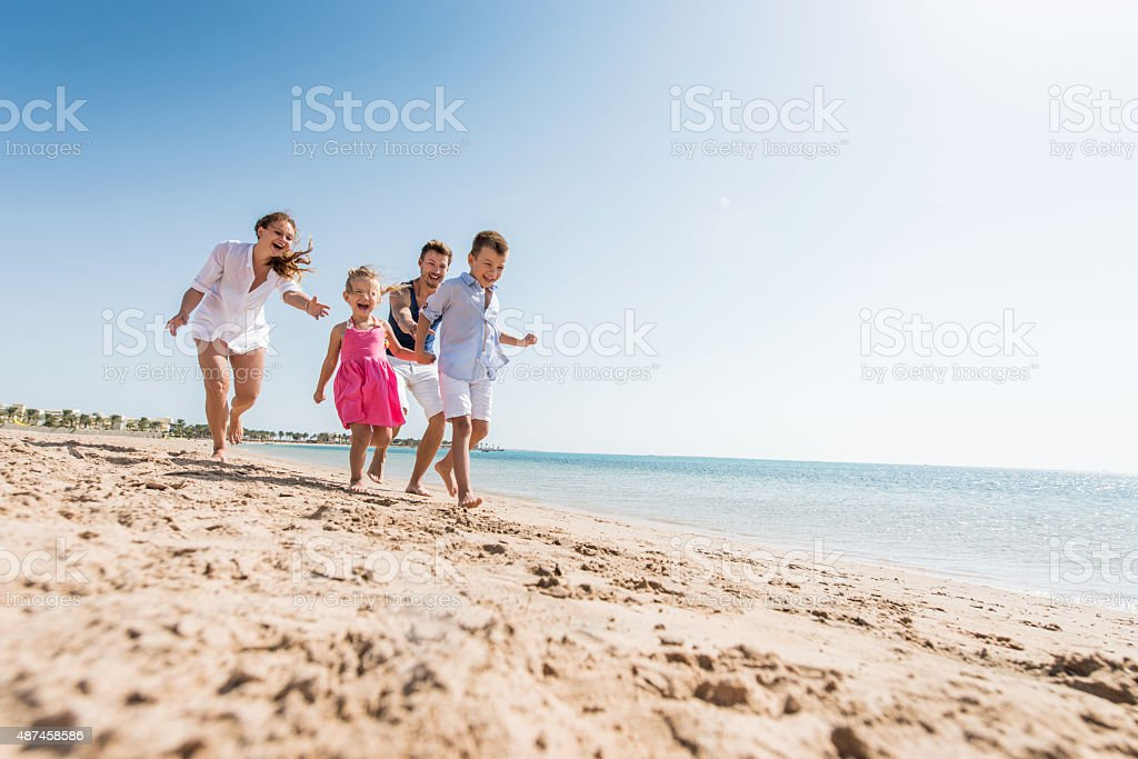 Young playful family chasing on the beach during summer day. stock photo