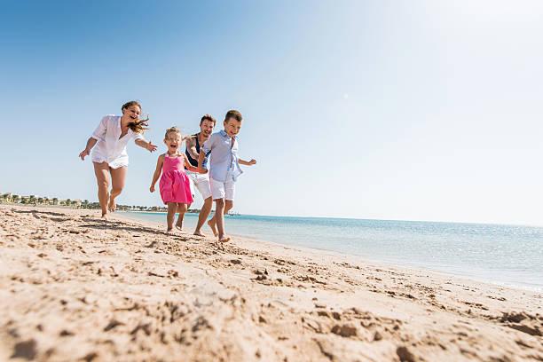 Jovem família divertida chasing na praia durante o dia de verão. - fotografia de stock