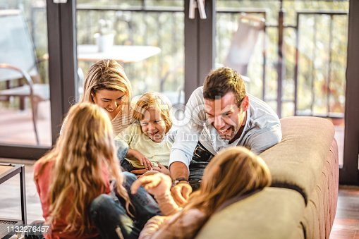 1159543952istockphoto Young playful family having fun in the living room. 1132276457