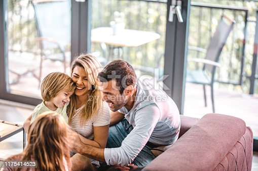 1159543952istockphoto Young playful family having fun in the living room. 1175414523