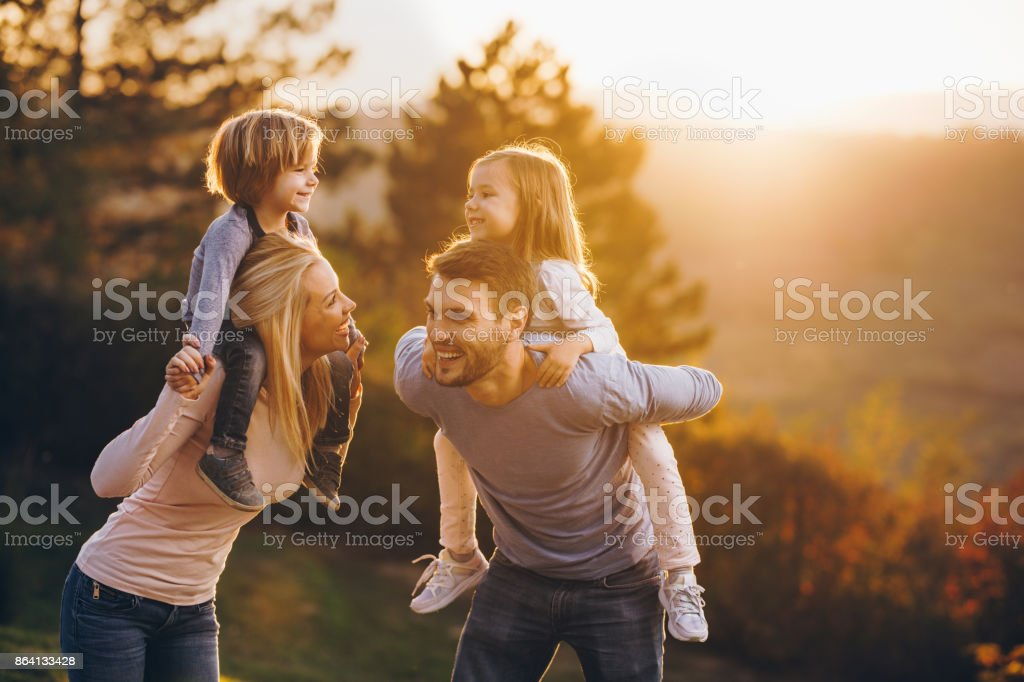Young playful family having fun in the park at sunset. royalty-free stock photo