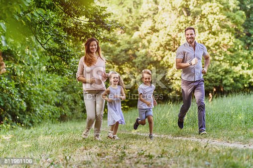658444674istockphoto Young playful family having fun running in nature 811961106