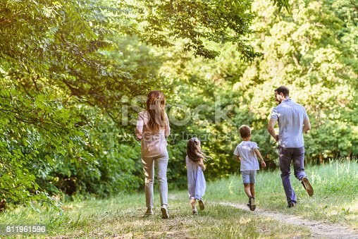658444674istockphoto Young playful family having fun running in nature 811961596
