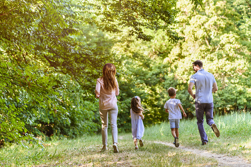 658444674 istock photo Young playful family having fun running in nature 811961596