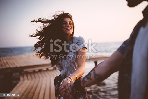 Young romantic hipster couple on summer island holidays holding hands and having fun on jetty