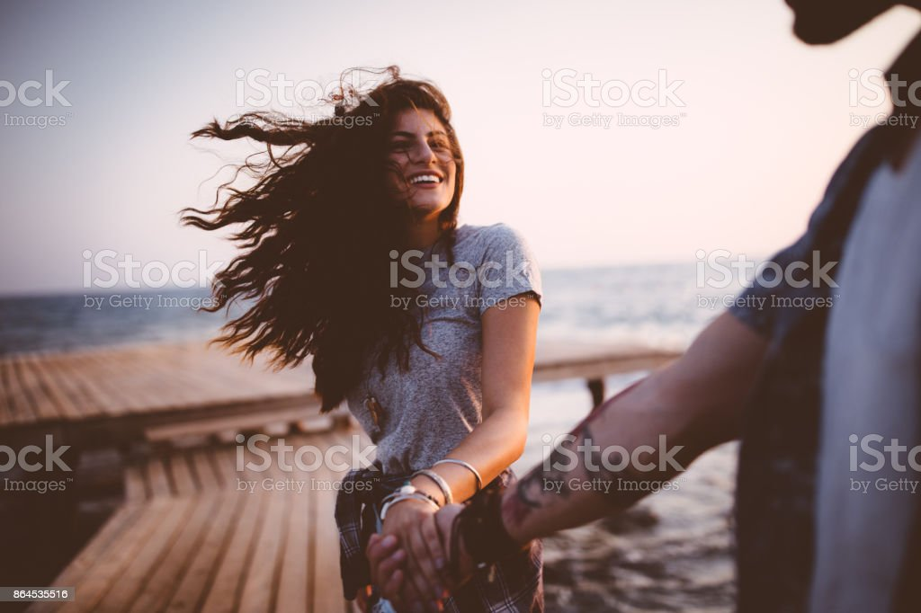 Young playful hipster couple holding hands on jetty at sunset stock photo
