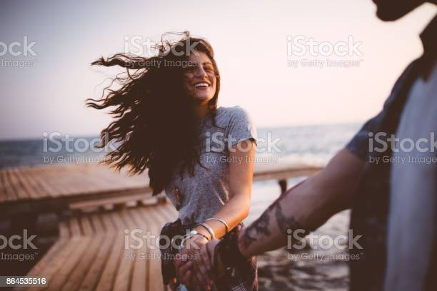 Photo of Young playful hipster couple holding hands on jetty at sunset