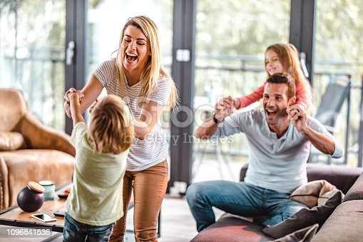 1159543952istockphoto Young playful parents having fun with their kids at home. 1096841536