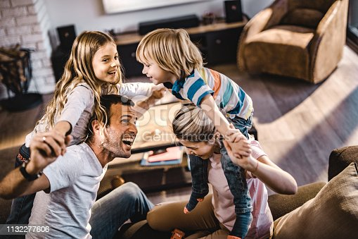 1159543952istockphoto Young playful parents having fun with their small kids at home. 1132277606