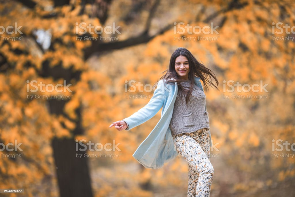 Young playful woman spinning in autumn day at the park. stock photo