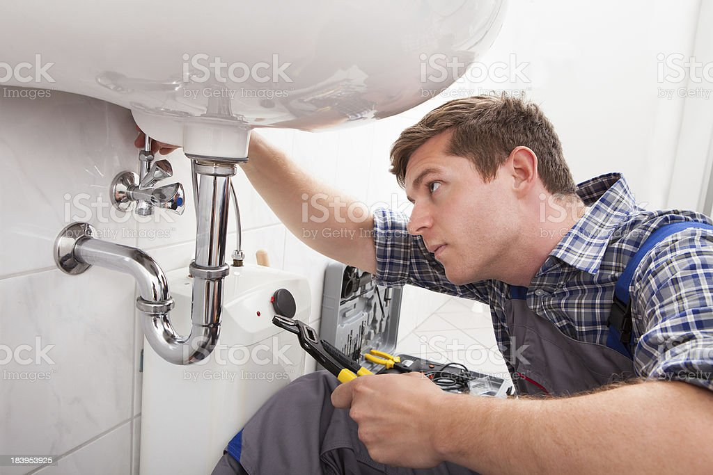 Young plumber fixing a sink in bathroom stock photo