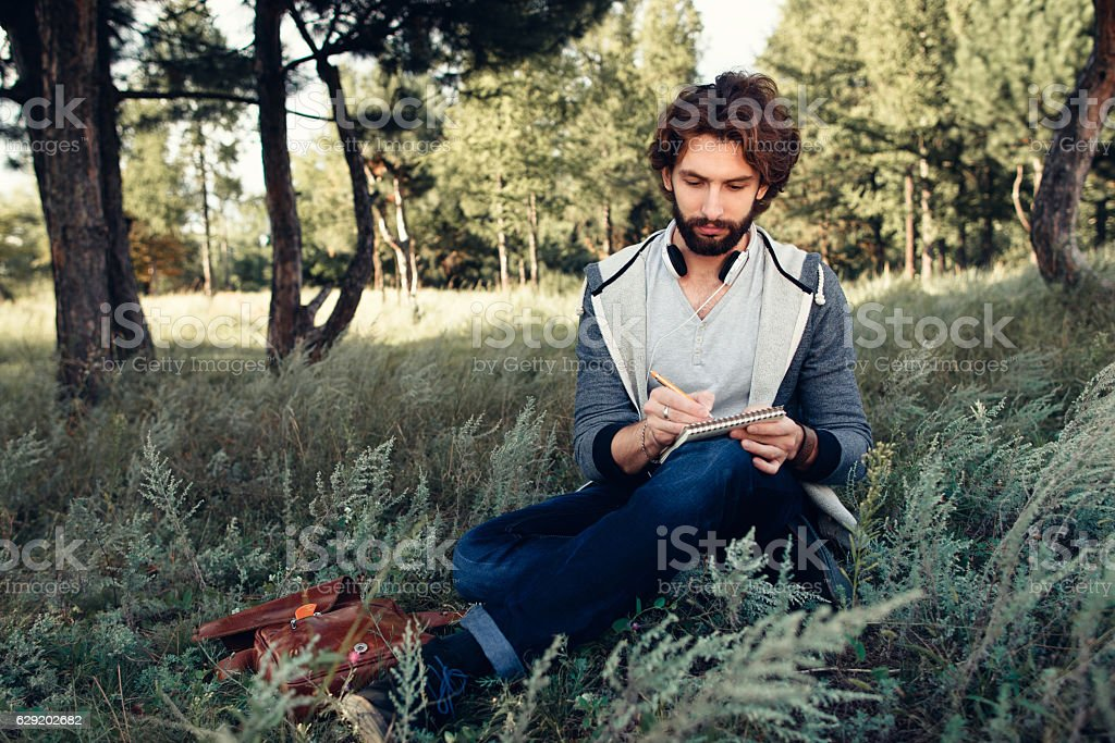 Young poet writing in his sketchbook in forest stock photo