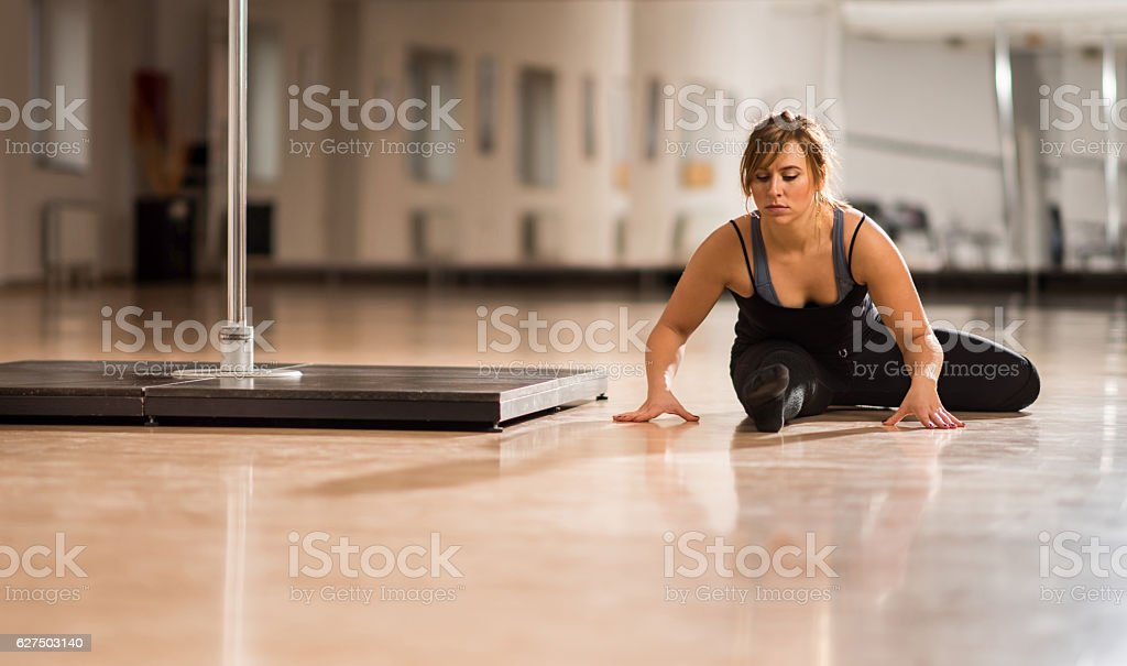 Young pole dancer doing stretching exercises in a dance studio. stock photo
