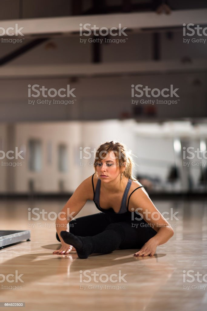 Young pole dancer doing stretching exercises in a dance studio. royalty-free stock photo