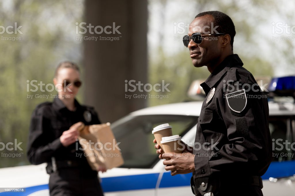Young Police Officers With Coffee To Go And Paper Bag With