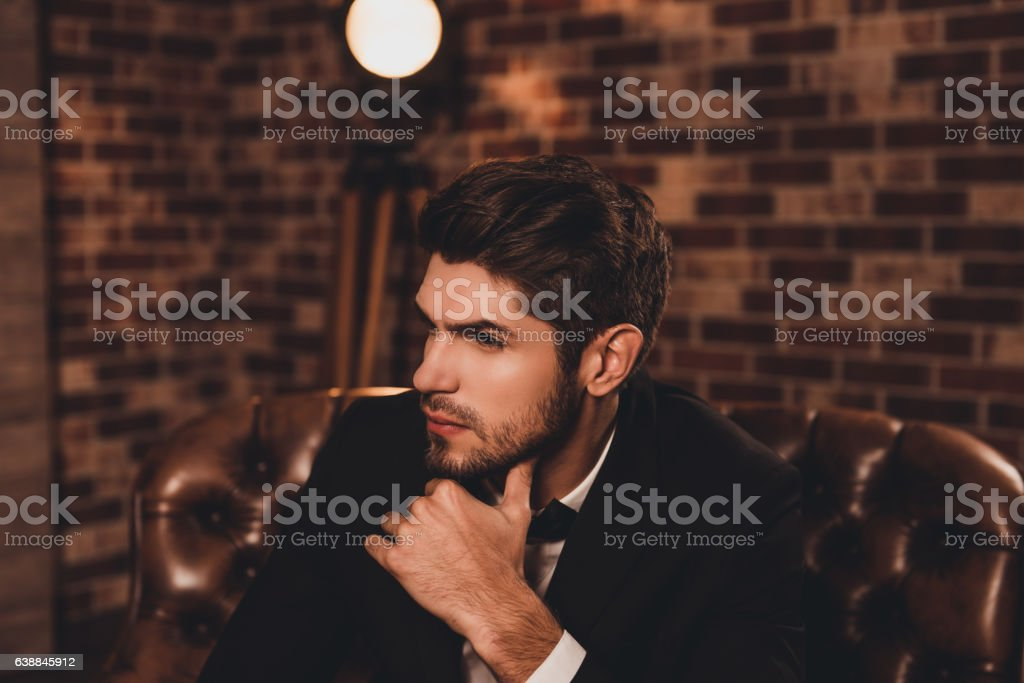 Young ponder businessman in tuxedo thinking about smth stock photo