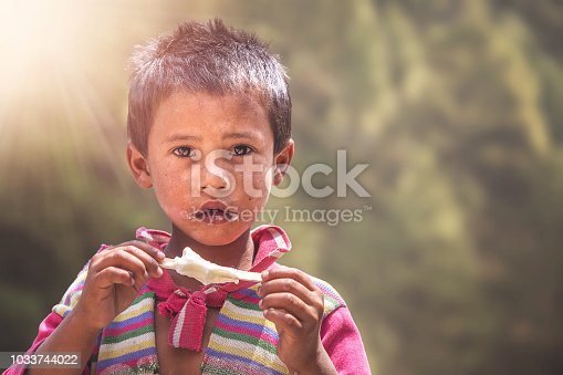 941788480 istock photo Young poor Indian street boy eating ice cream on a street. 1033744022