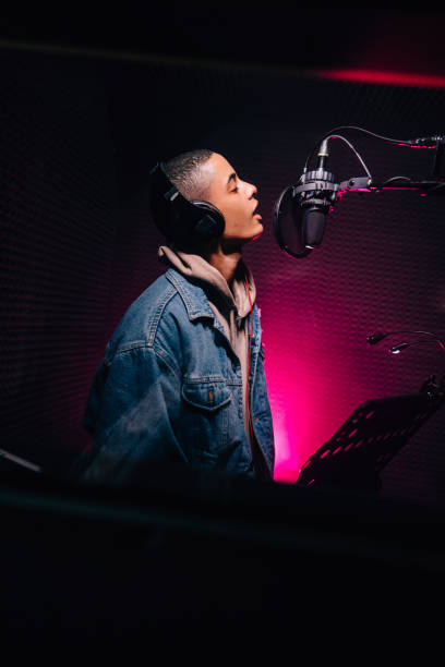 Young pop musician singing and recording song in music studio stock photo