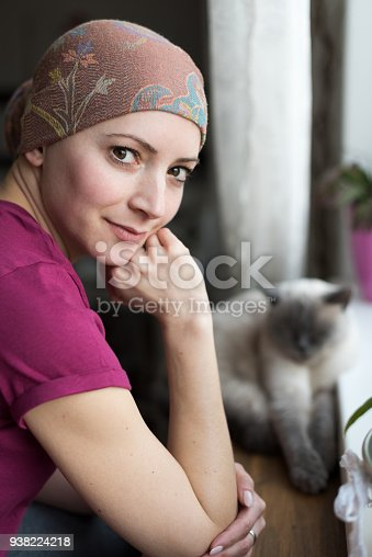 469949126 istock photo Young positive adult female cancer patient sitting in the kitchen by a window with her pet cat, smiling and looking at the camera. 938224218