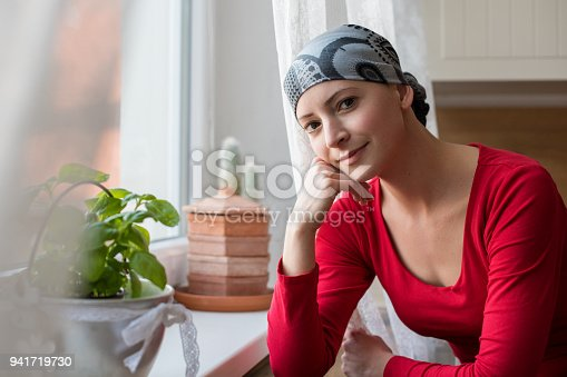 469949126 istock photo Young positive adult female cancer patient sitting in the kitchen by a window, smiling and looking at the camera. 941719730