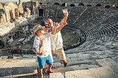 Young positive family take a self photo on the antique amphitheater in Side, Turkey