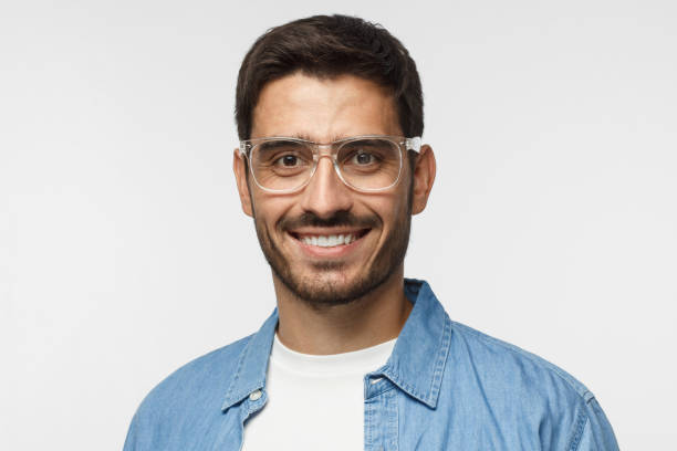 Young positive man with eyeglasses, dressed in light blue shirt and white t-shirt, looking at camera with happy smile, isolated on gray background stock photo