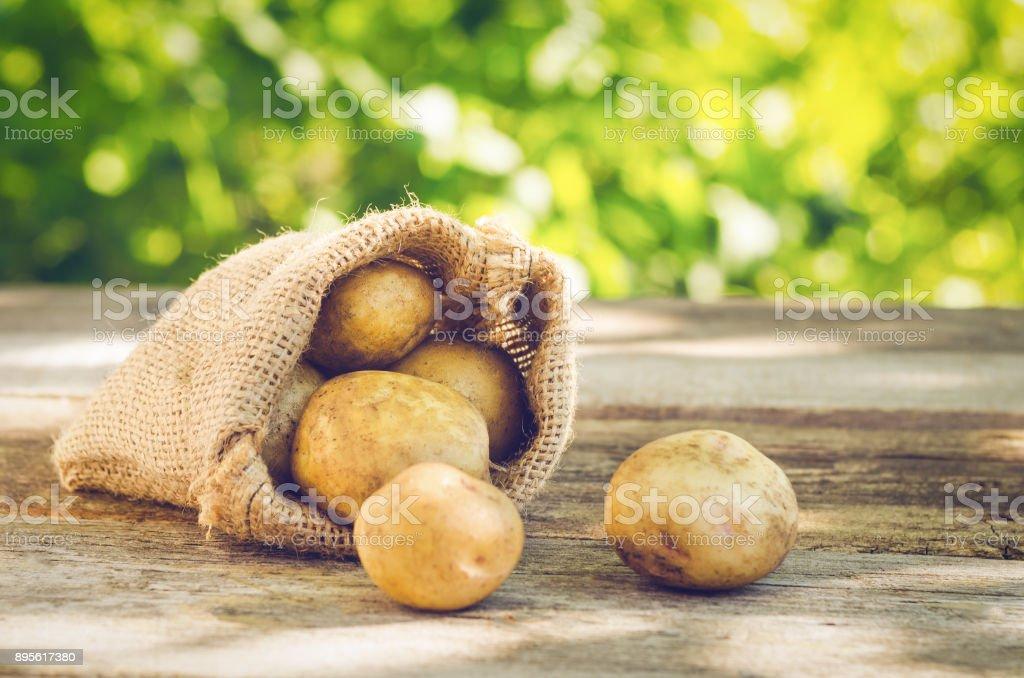 Jovens batatas em um saco em uma mesa de madeira - foto de acervo