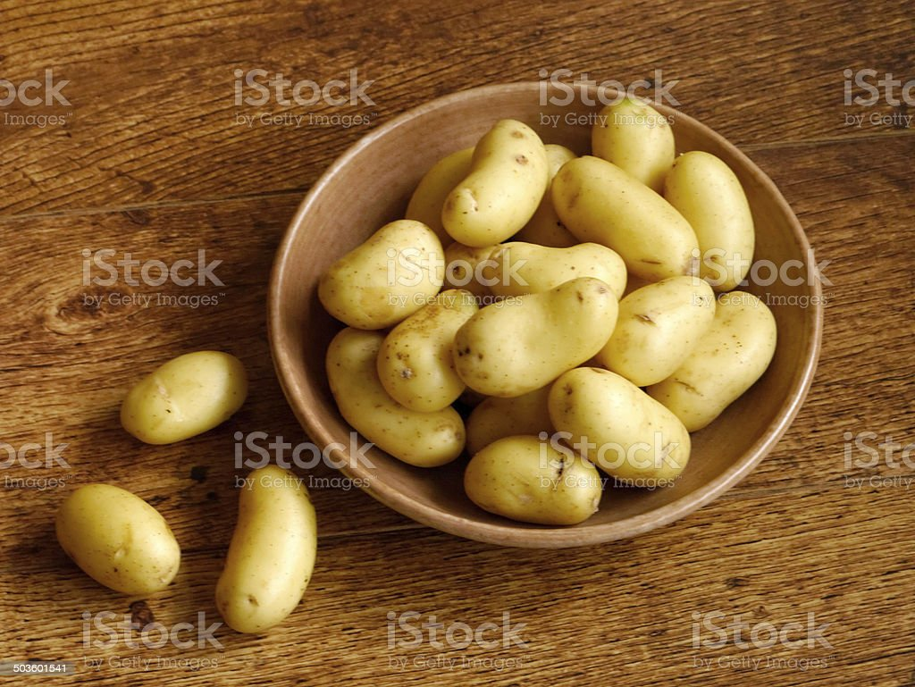 Young potatoes in bowl on wooden table stock photo