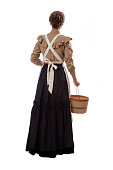 istock Young prairie woman holding a basket walking away isolated on white 1313028887