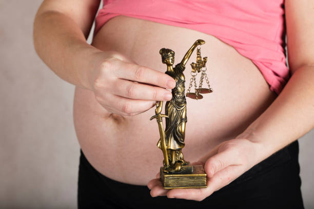 Young pregnant between 30 and 35 years old woman keeps statue of Themis. stock photo
