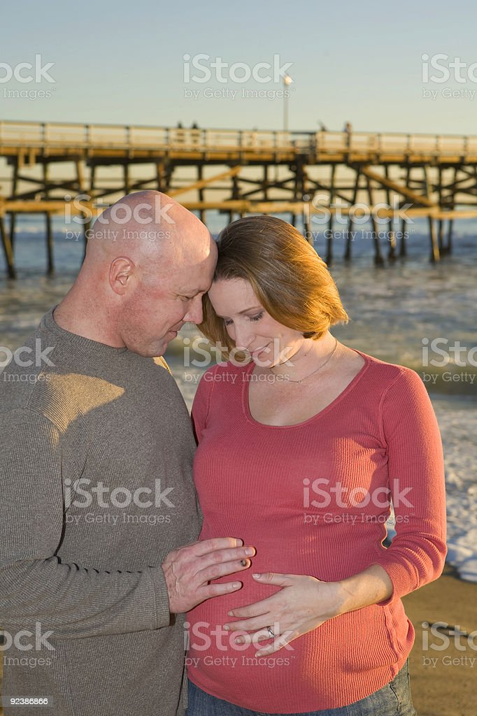 Young Pregnant Couple looking down stock photo