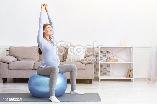 istock Young pregnant girl sitting on fit ball at home 1191860035