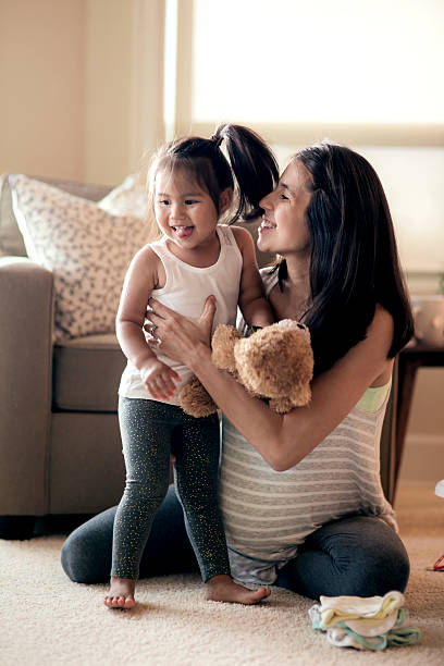 Young pregnant mother holding and laughing with her young daughter stock photo